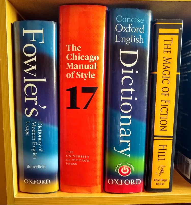 A bookshelf showing the spines of Fowler's, CMOS 17, Concise OED, and The Magic of Fiction.